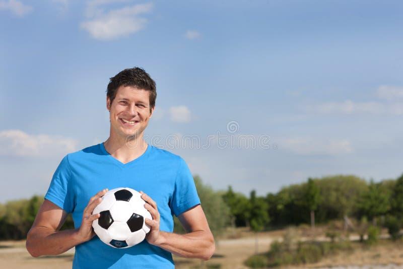 Hombre joven con el balón de fútbol imagen de archivo