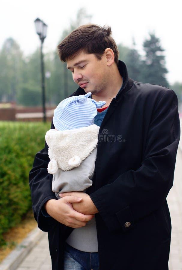 Hombre joven con el bebé en una honda imagen de archivo libre de regalías