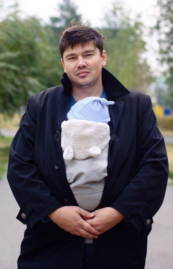Hombre joven con el bebé en una honda fotos de archivo