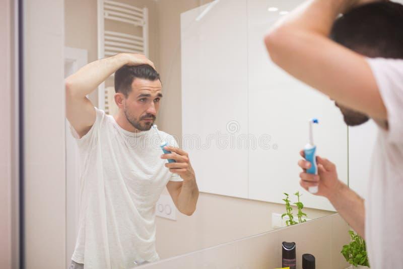 Hombre joven con el cepillo de dientes eléctrico imagen de archivo