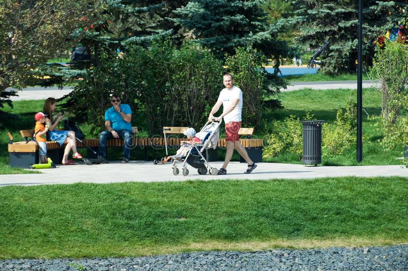 Hombre joven con el cochecito de los niños que camina en el parque de Butovo, Moscú, Rusia imagenes de archivo