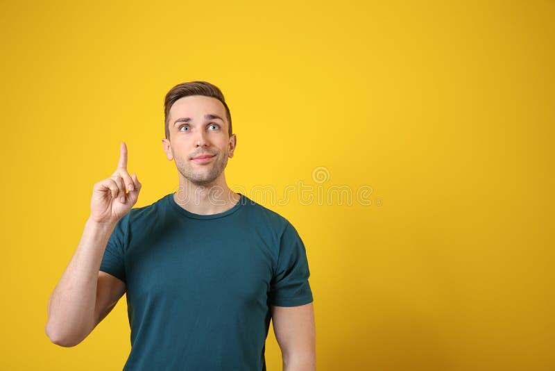 Hombre joven con el dedo índice aumentado en fondo del color fotos de archivo libres de regalías