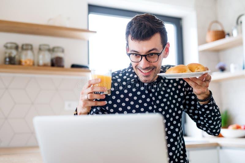 Hombre joven con el desayuno y el ordenador portátil, un concepto de Ministerio del Interior imagen de archivo