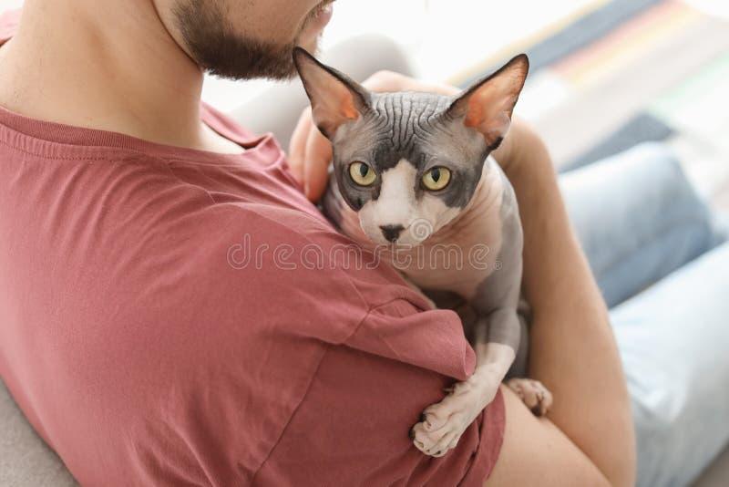 Hombre joven con el gato lindo imagen de archivo