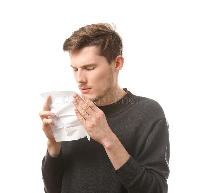Hombre joven con el limpiador de la nariz en el fondo blanco Concepto de la alergia fotos de archivo