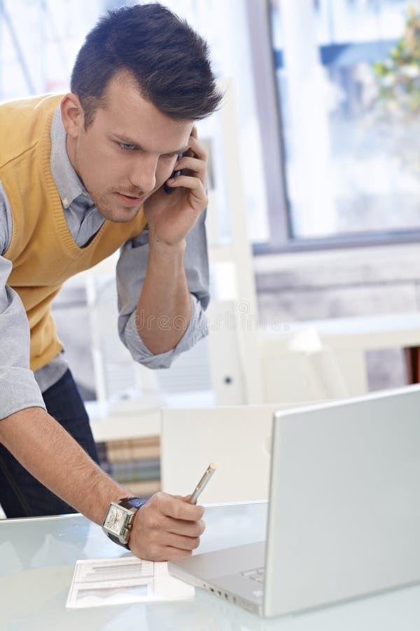 Hombre joven con el móvil y la computadora portátil fotos de archivo libres de regalías