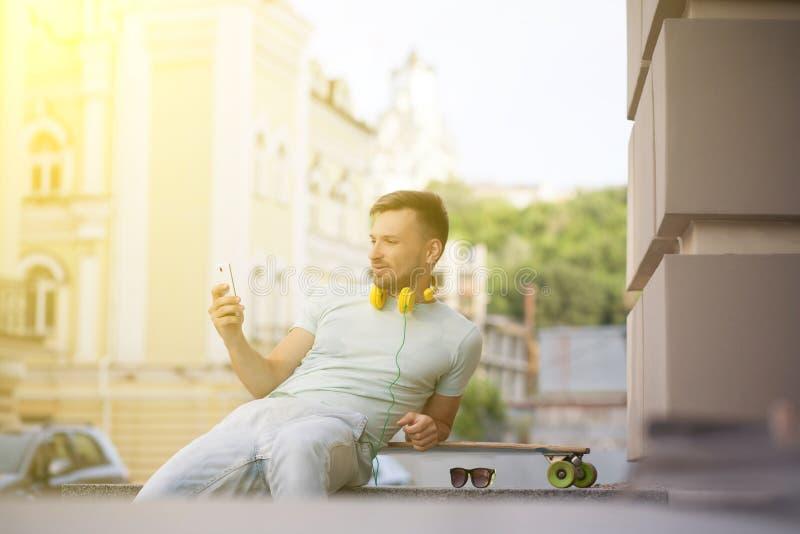 Hombre joven con el monopatín foto de archivo