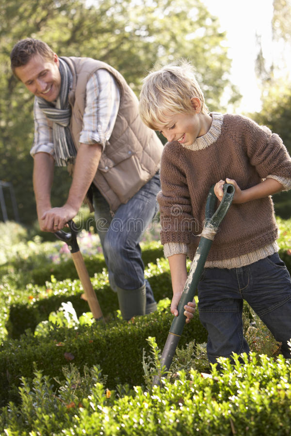 Hombre joven con el niño que trabaja en jardín fotografía de archivo