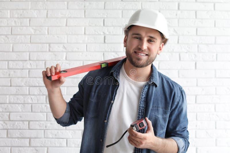 Hombre joven con el nivel de la construcción y cinta métrica foto de archivo libre de regalías
