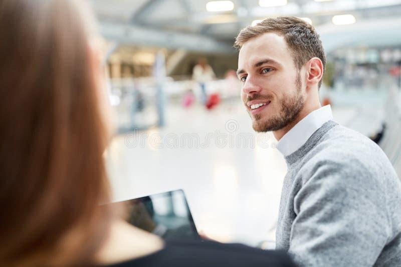 Hombre joven con el ordenador portátil en el aeropuerto imagenes de archivo