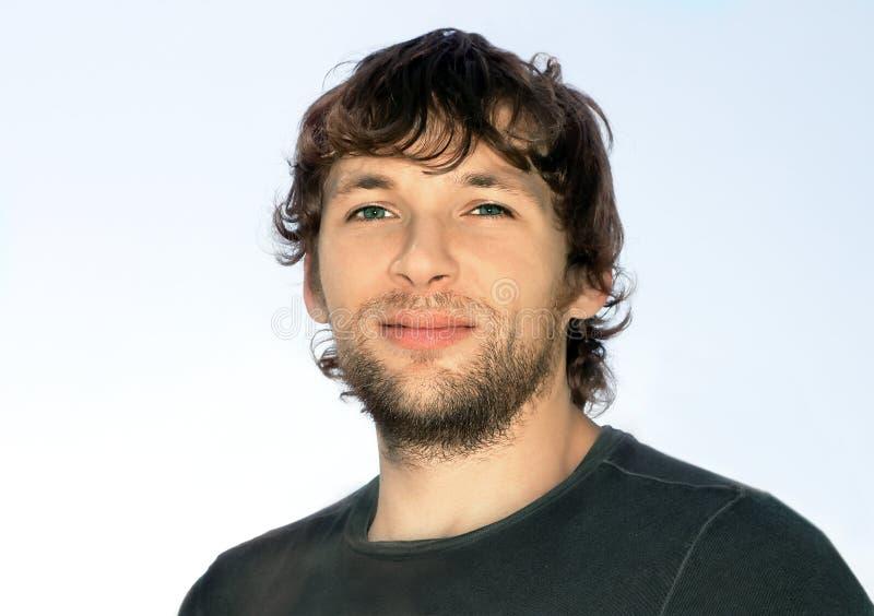 Hombre joven con el pelo rizado y la cara de la barba imagen de archivo