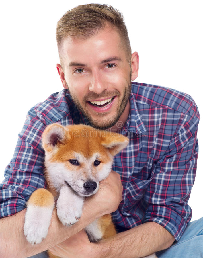 Hombre joven con el pequeño perrito lindo de Akita Inu imagen de archivo