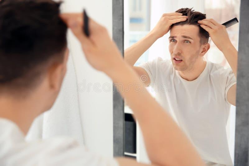 Hombre joven con el problema de la pérdida de pelo que mira en espejo imagenes de archivo