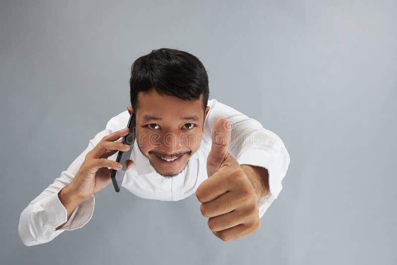 Hombre joven con el pulgar de la demostración del smartphone para arriba foto de archivo