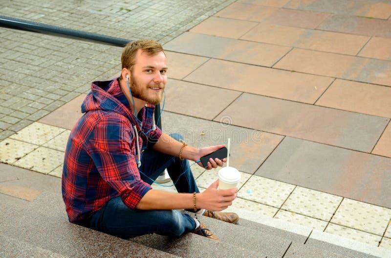 Hombre joven con el refresco que se sienta en las escaleras y que usa su teléfono imagen de archivo libre de regalías
