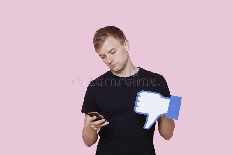 Hombre joven con el teléfono celular que sostiene el botón falso de la aversión contra fondo rosado fotografía de archivo