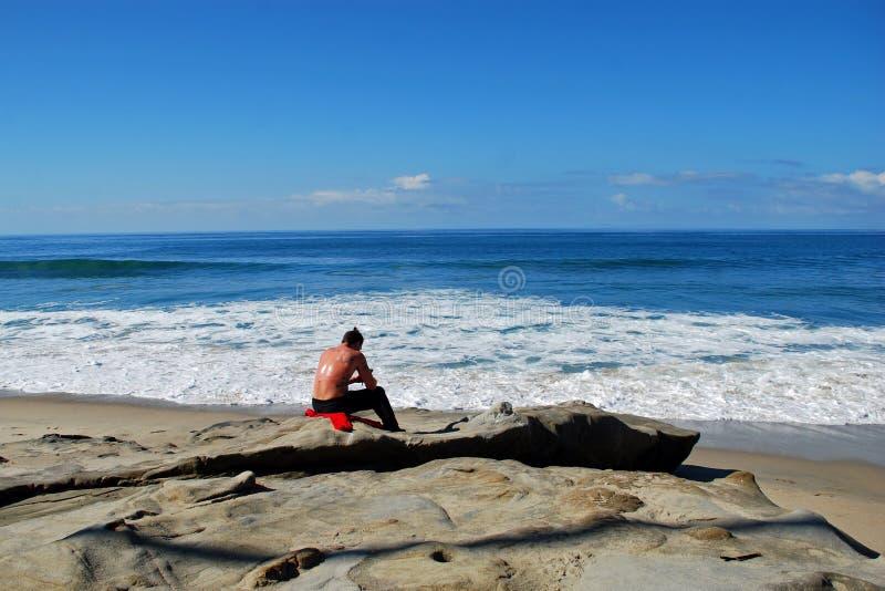 Hombre joven con el teléfono elegante en Laguna Beach, California fotografía de archivo