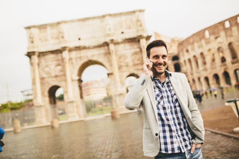 Hombre joven con el teléfono móvil en la calle en Roma, Italia imágenes de archivo libres de regalías