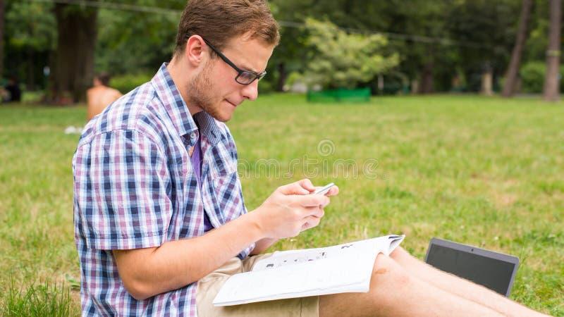 Hombre joven con el teléfono móvil que se sienta en una hierba. imagen de archivo