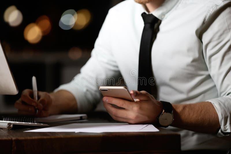 Hombre joven con el teléfono móvil que trabaja en oficina en la noche foto de archivo libre de regalías