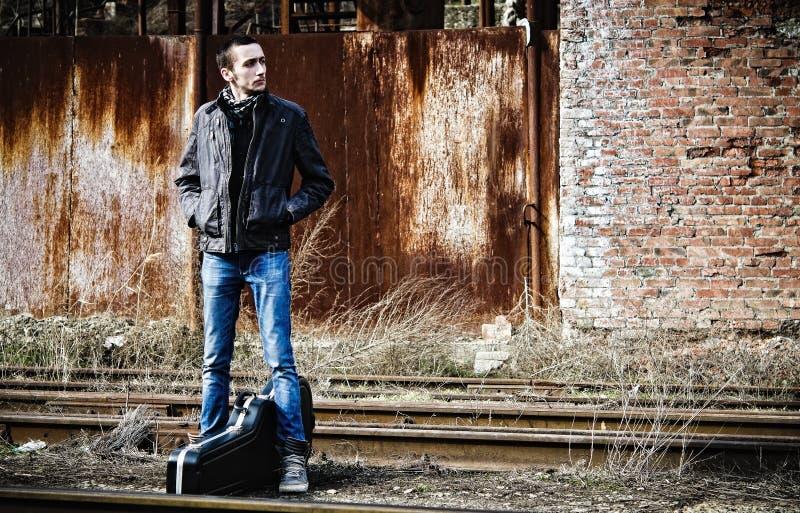 Hombre joven con el tren que espera de la caja de la guitarra para entre ruinas industriales foto de archivo