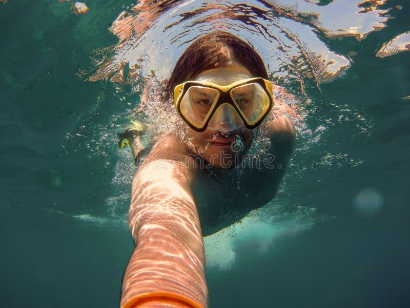 Hombre joven con el tubo respirador y la natación de la máscara que se zambulle y tomar un selfie debajo del agua Concepto del vi imágenes de archivo libres de regalías