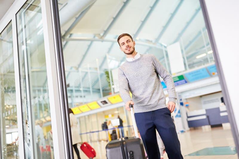 Hombre joven con equipaje en el terminal de aeropuerto imagen de archivo