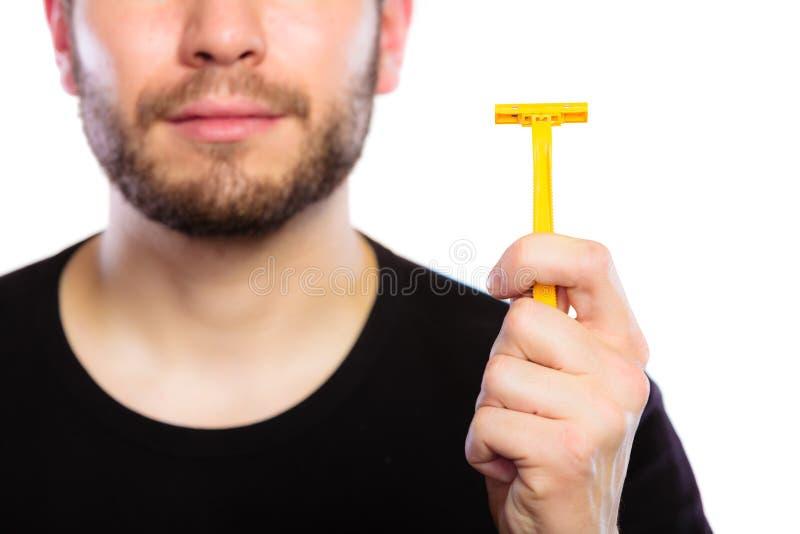 Hombre joven con la barba que muestra la hoja de afeitar imagen de archivo libre de regalías