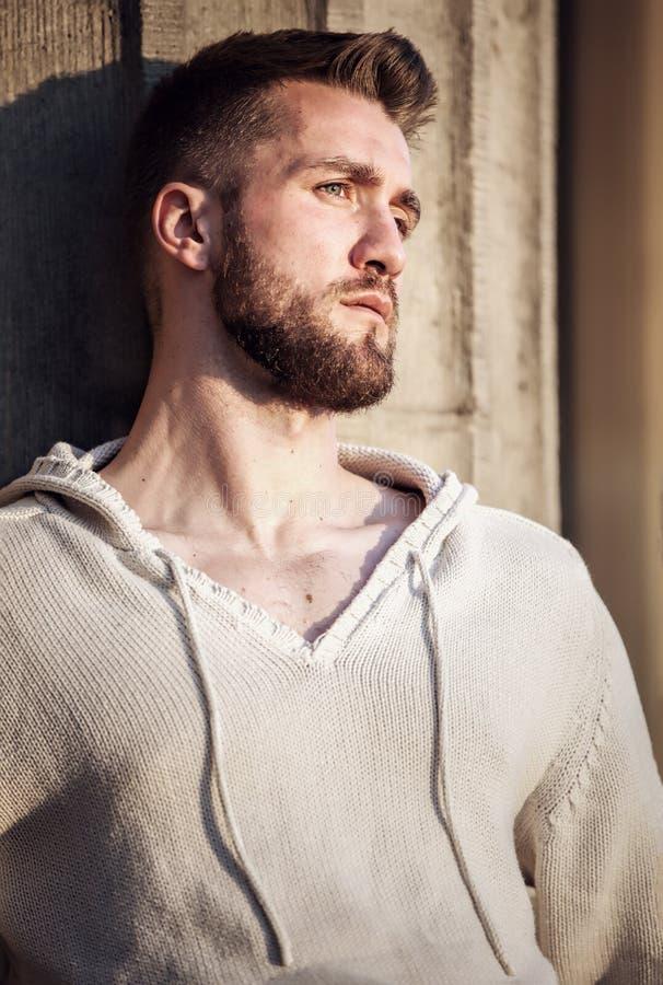 Hombre joven con la barba que se inclina contra una pared imagen de archivo