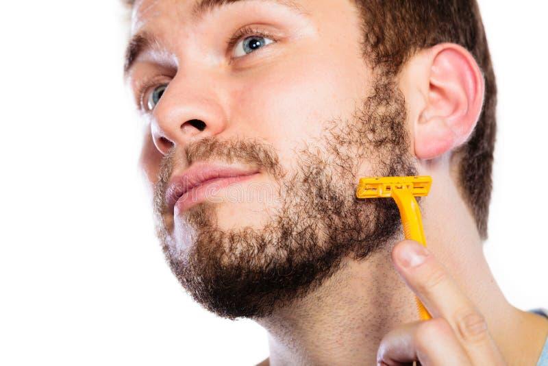 Hombre joven con la barba que sostiene la hoja de afeitar fotos de archivo