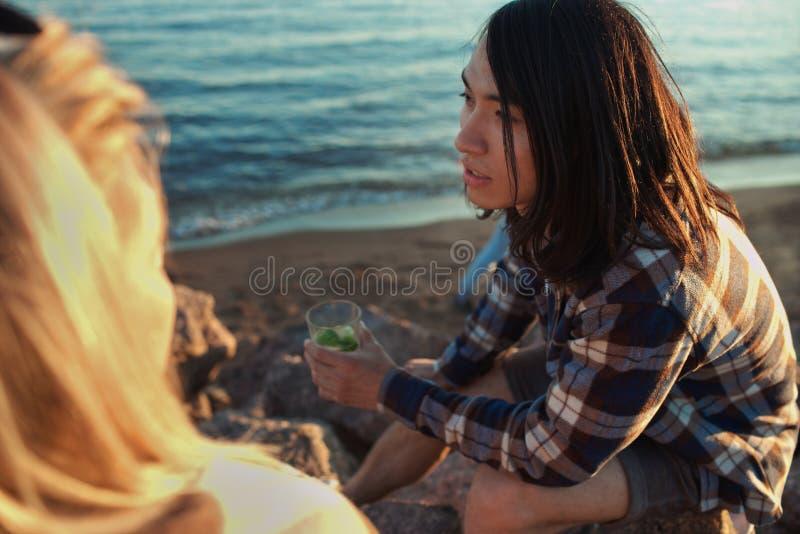 Hombre joven con la bebida en la playa imagen de archivo