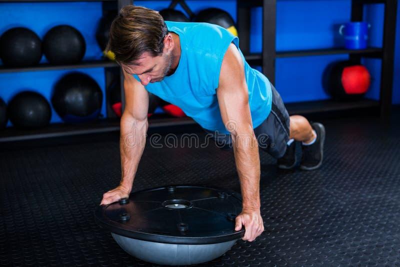 Hombre joven con la bola de BOSU en gimnasio fotos de archivo