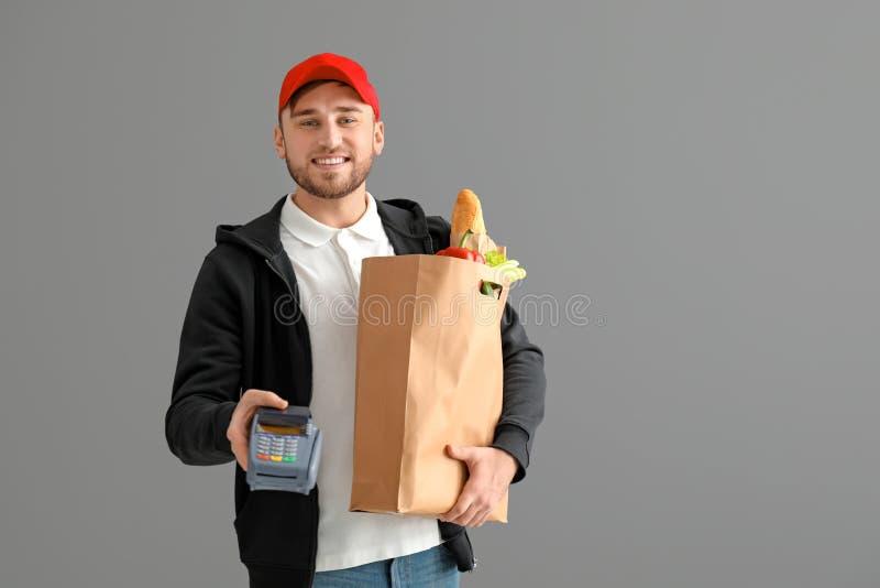 Hombre joven con la bolsa de papel y terminal del banco en fondo gris Servicio de entrega de la comida imagen de archivo libre de regalías