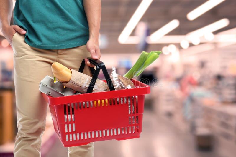 Hombre joven con la cesta de compras por completo de diversos productos en el supermercado, primer fotografía de archivo libre de regalías
