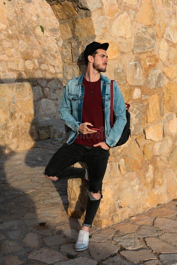 Hombre joven con la chaqueta y el casquillo con el castillo en fondo imagenes de archivo