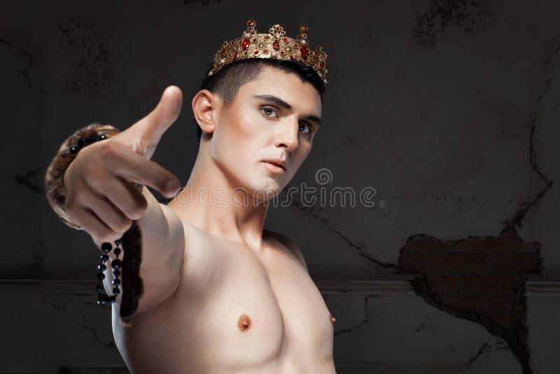 Hombre joven con la corona en la cabeza que señala su finger fotografía de archivo libre de regalías