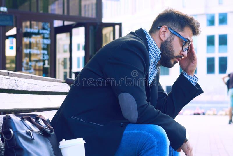 Hombre joven con la expresión facial triste que se sienta en un banco en el parque El oficinista perdió su trabajo Desesperación  fotos de archivo