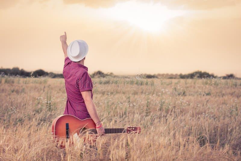Hombre joven con la guitarra acústica que disfruta de la puesta del sol imagen de archivo