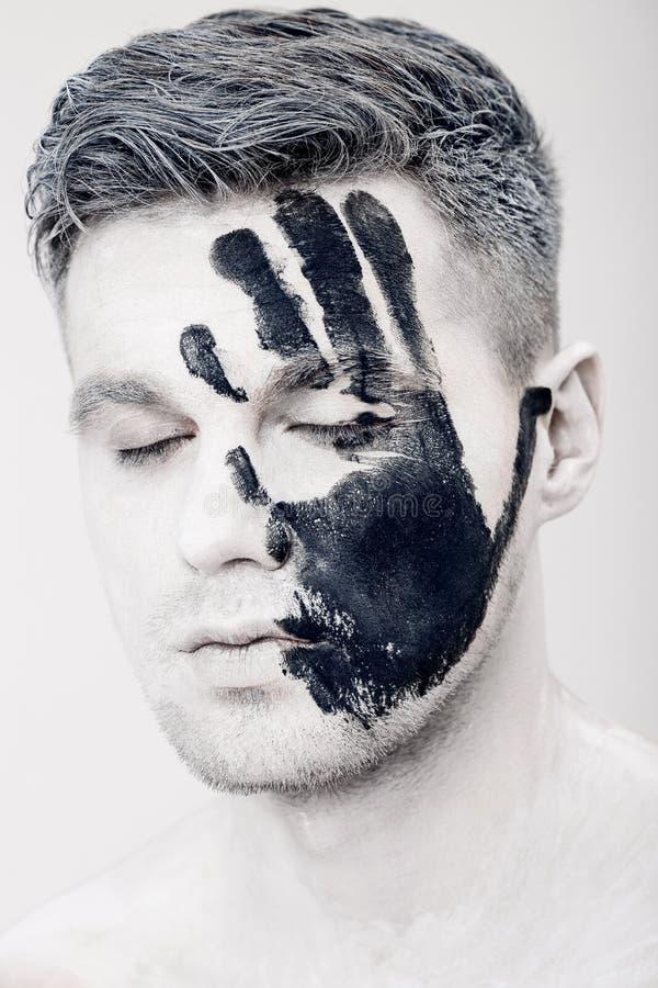 Hombre joven con la impresión de la mano negra en la cara blanca Retrato del primer Maquillaje profesional de la moda Maquillaje  foto de archivo libre de regalías