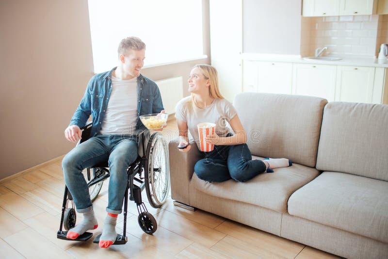 Hombre joven con la incapacidad que se sienta al lado de mujer en el sof? Miran uno a y sile Pel?cula de observaci?n Cine casero imagen de archivo libre de regalías