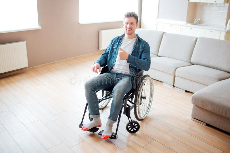 Hombre joven con la incapacidad que se sienta en la silla de ruedas Solamente en sitio vac?o grande Deteniendo el pulgar grande y fotos de archivo libres de regalías