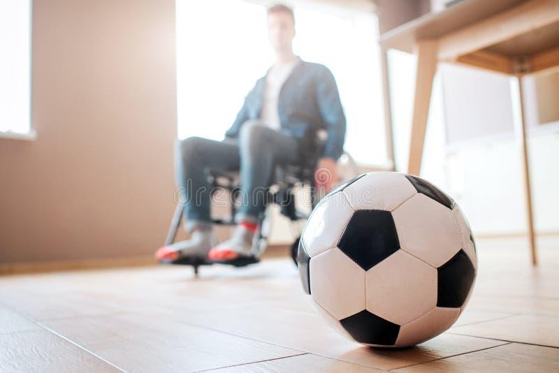 Hombre joven con la incapacidad que se sienta en la silla de ruedas y mirar abajo la bola para el juego Ex deportista Trastornado imágenes de archivo libres de regalías