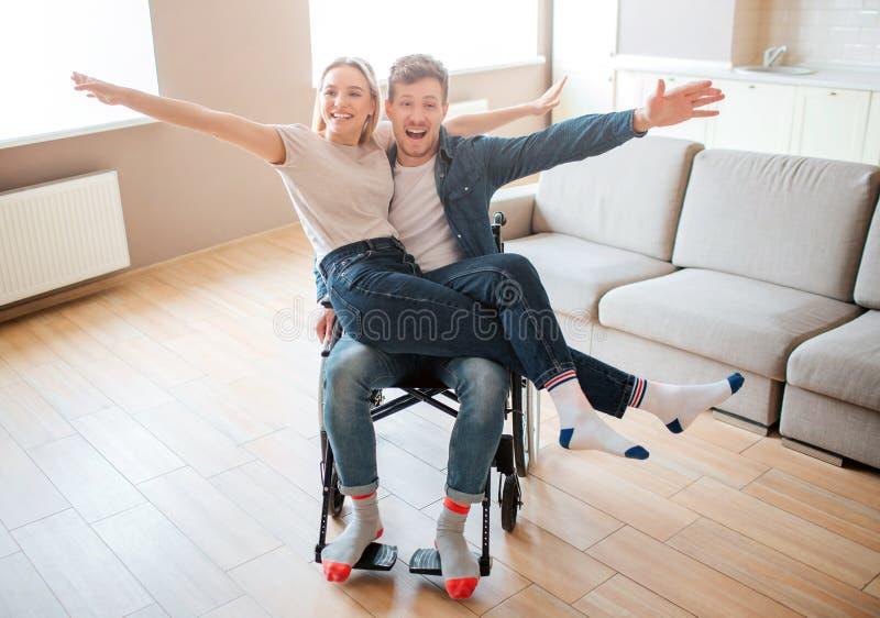 Hombre joven con la incapacidad y la integraci?n que llevan a cabo el girlfirend en rodillas Sonr?en y presentan en c?mara Feliz  foto de archivo libre de regalías