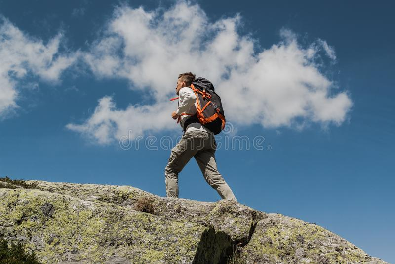 Hombre joven con la mochila grande que camina para alcanzar el top de la montaña durante un día soleado fotografía de archivo libre de regalías