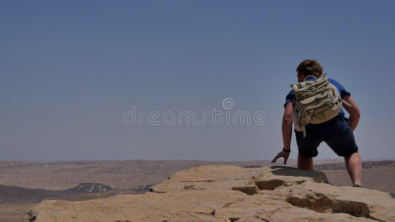Hombre joven con la mochila que se sienta en el borde del ` s del acantilado y que mira el desierto imágenes de archivo libres de regalías