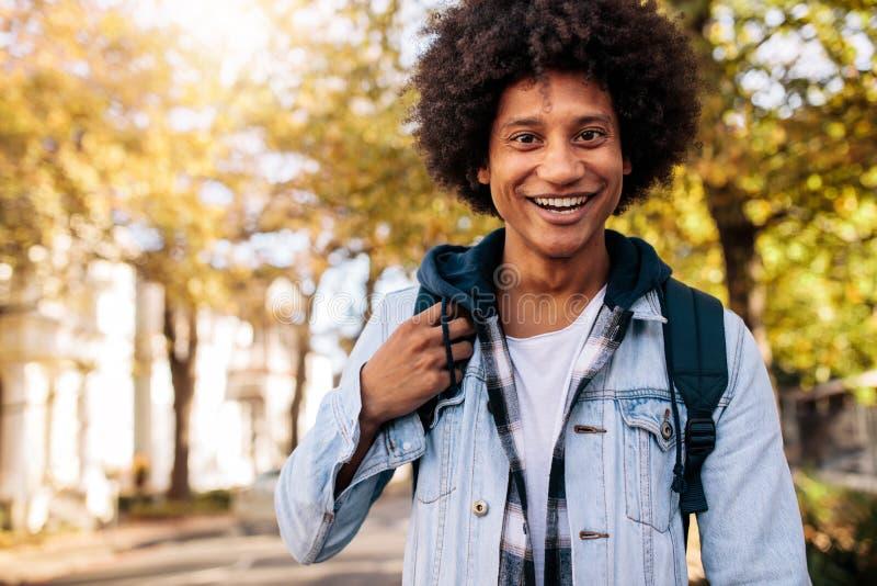 Hombre joven con la mochila que va a la universidad de la escuela foto de archivo libre de regalías