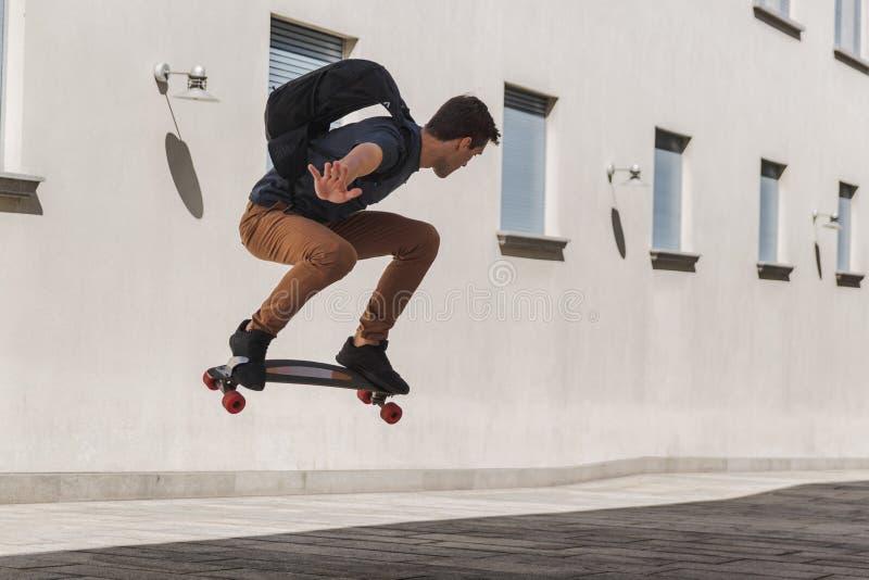 Hombre joven con la mochila usando longboard y el salto cuando él va a enseñar después de vacaciones de verano foto de archivo