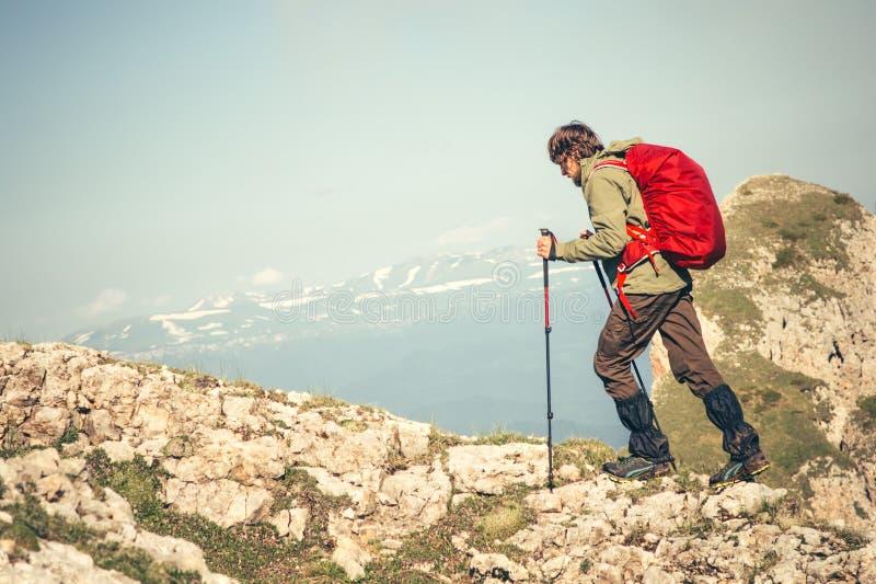 Hombre joven con la mochila y funcionamiento de los polos del senderismo al aire libre imagen de archivo libre de regalías