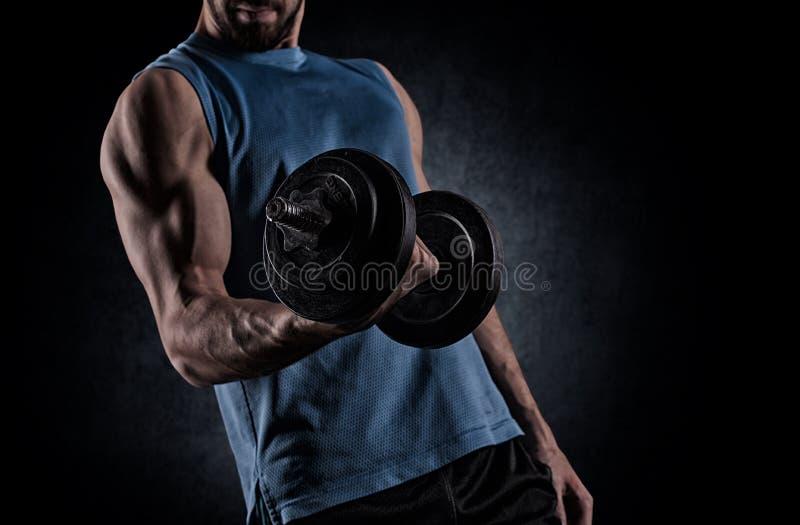 Hombre joven con la pesa de gimnasia que dobla los músculos sobre fondo gris fotografía de archivo libre de regalías