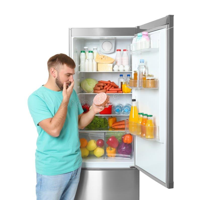 Hombre joven con la salchicha expirada cerca del refrigerador abierto fotografía de archivo libre de regalías